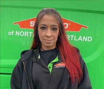 woman with red hair stands in front of green SERVPRO vehicle