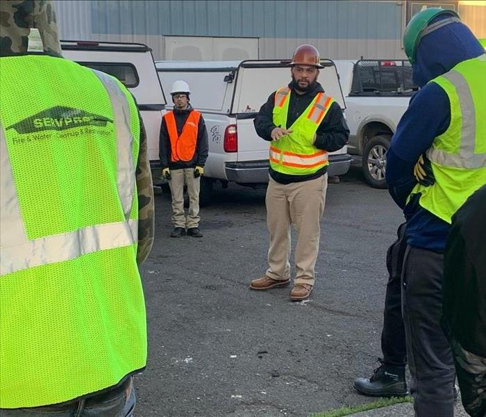 Project Manager speaks with group of workers in safety vests