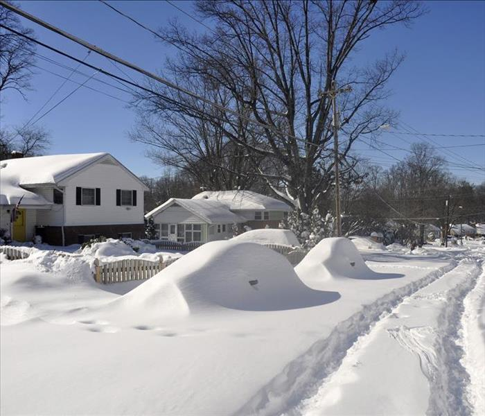 Snow covers residential street, piles up in front of residential home.