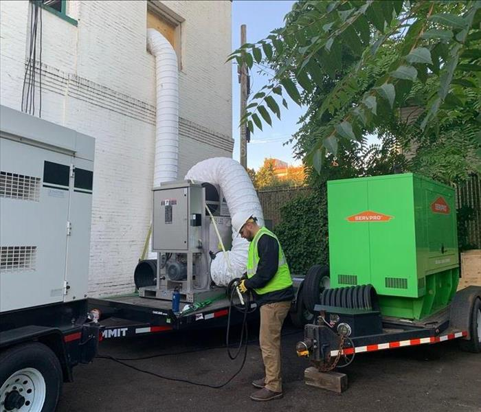 Two generators sit on trailers, one large desiccant sits on a trailer with tubing connected to a commercial building.